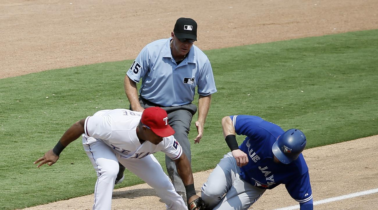 Texas Rangers third baseman Adrian Beltre, left, is unable to tag out Toronto Blue Jays' Josh Donaldson, right, who steals the bag as umpire Ed Hickox, center, watches in the sixth inning of a baseball game Thursday, Aug. 27, 2015, in Arlington, Texas. (A
