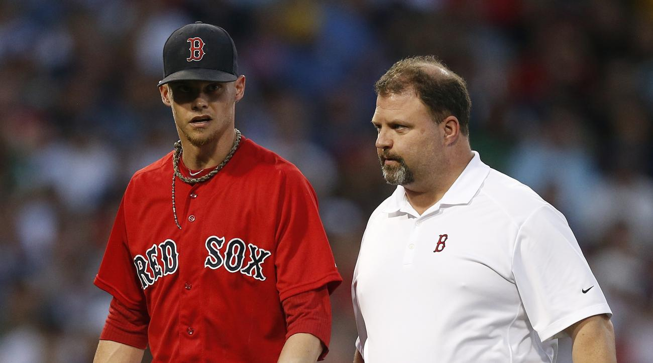Boston Red Sox's Clay Buchholz, left, leaves the baseball game with a trainer during the fourth inning of a baseball game against the New York Yankees in Boston, Friday, July 10, 2015. (AP Photo/Michael Dwyer)