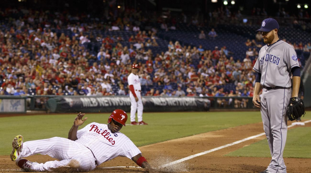 Philadelphia Phillies' Ryan Howard, left, slides safely into home on a wild pitch by San Diego Padres starting pitcher Ian Kennedy, right, during the fourth inning of a baseball game, Friday, Aug. 28, 2015, in Philadelphia. (AP Photo/Chris Szagola)