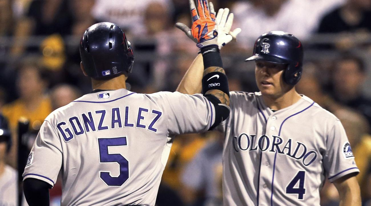 Colorado Rockies' Carlos Gonzalez, left, is greeted by on-deck batter Nick Hundley after hitting a solo home run against the Pittsburgh Pirates during the sixth inning of a baseball game, Friday, Aug. 28, 2015, in Pittsburgh. (AP Photo/Keith Srakocic)