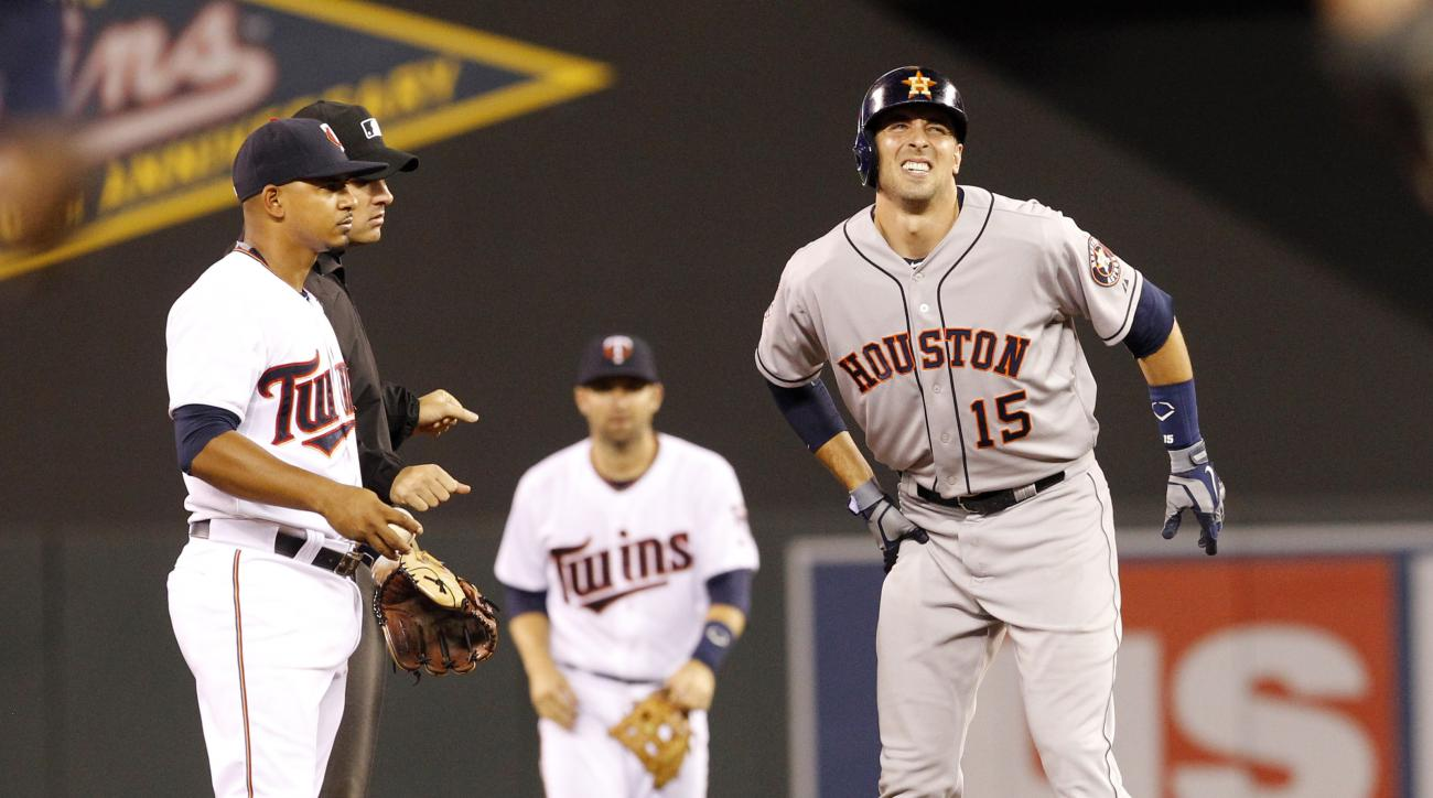 Houston Astros' Jason Castro (15) reacts after injuring his leg while advancing to second base on a double as Minnesota Twins shortstop Eduardo Escobar, left, and umpire Mark Ripperger step away during the fifth inning of a baseball game in Minneapolis, F