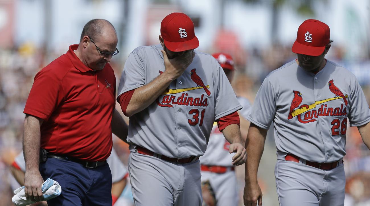 St. Louis Cardinals pitcher Lance Lynn (31) walks off the field with a trainer, left, and manager Mike Matheny, right, after injuring himself while throwing to first base in the eighth inning of a baseball game against the San Francisco Giants, Saturday,