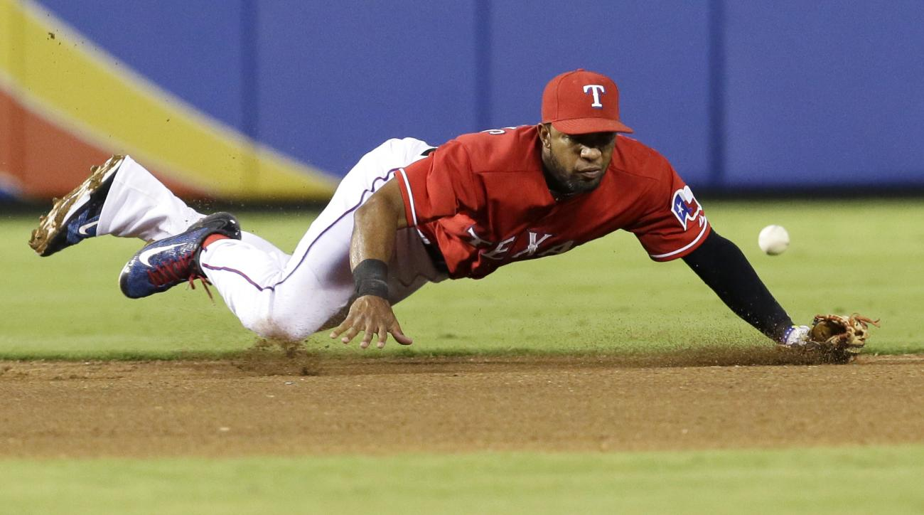 Texas Rangers shortstop Elvis Andrus can't get a handle on a grounder by Baltimore Orioles' Adam Jones that went for a single during the fourth inning of a baseball game in Arlington, Texas, Saturday, Aug. 29, 2015. (AP Photo/LM Otero)