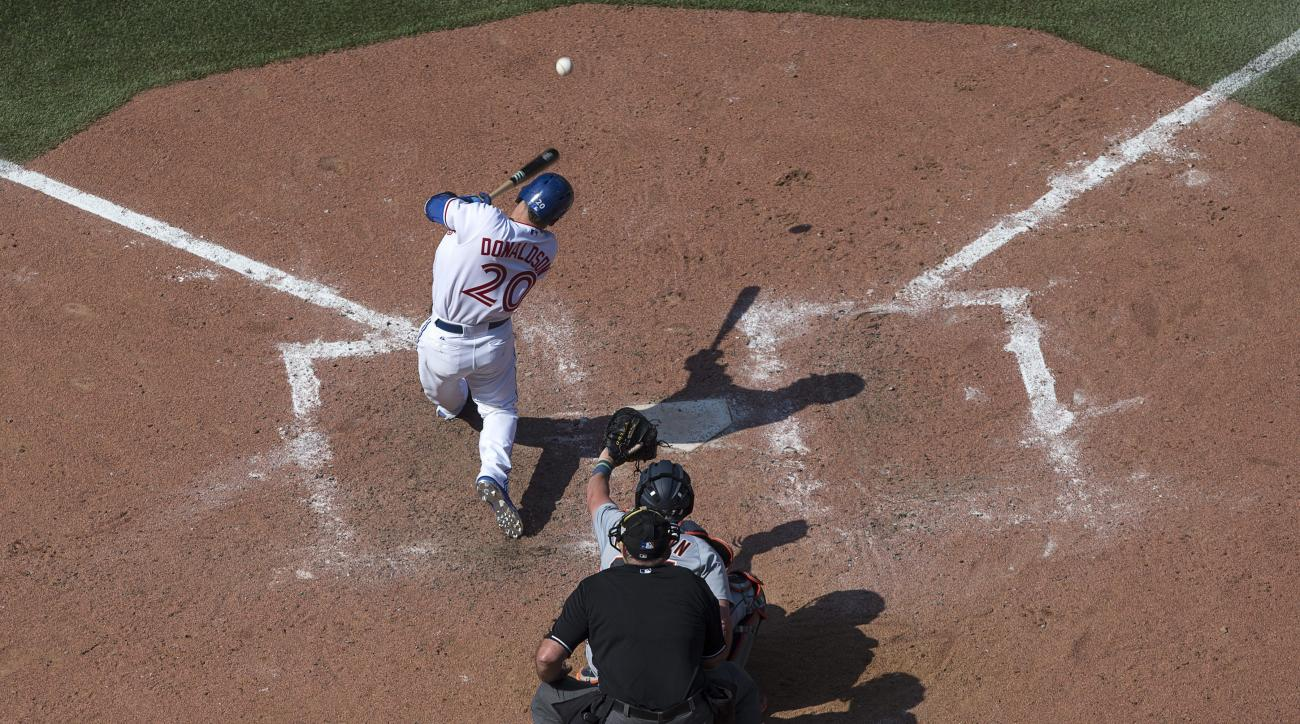 Toronto Blue Jays' Josh Donaldson, top, hits an RBI-single to drive in Ryan Goins during eighth-inning baseball game action against the Detroit Tigers in Toronto, Sunday, Aug. 30, 2015. (Chris Young/The Canadian Press via AP) MANDATORY CREDIT