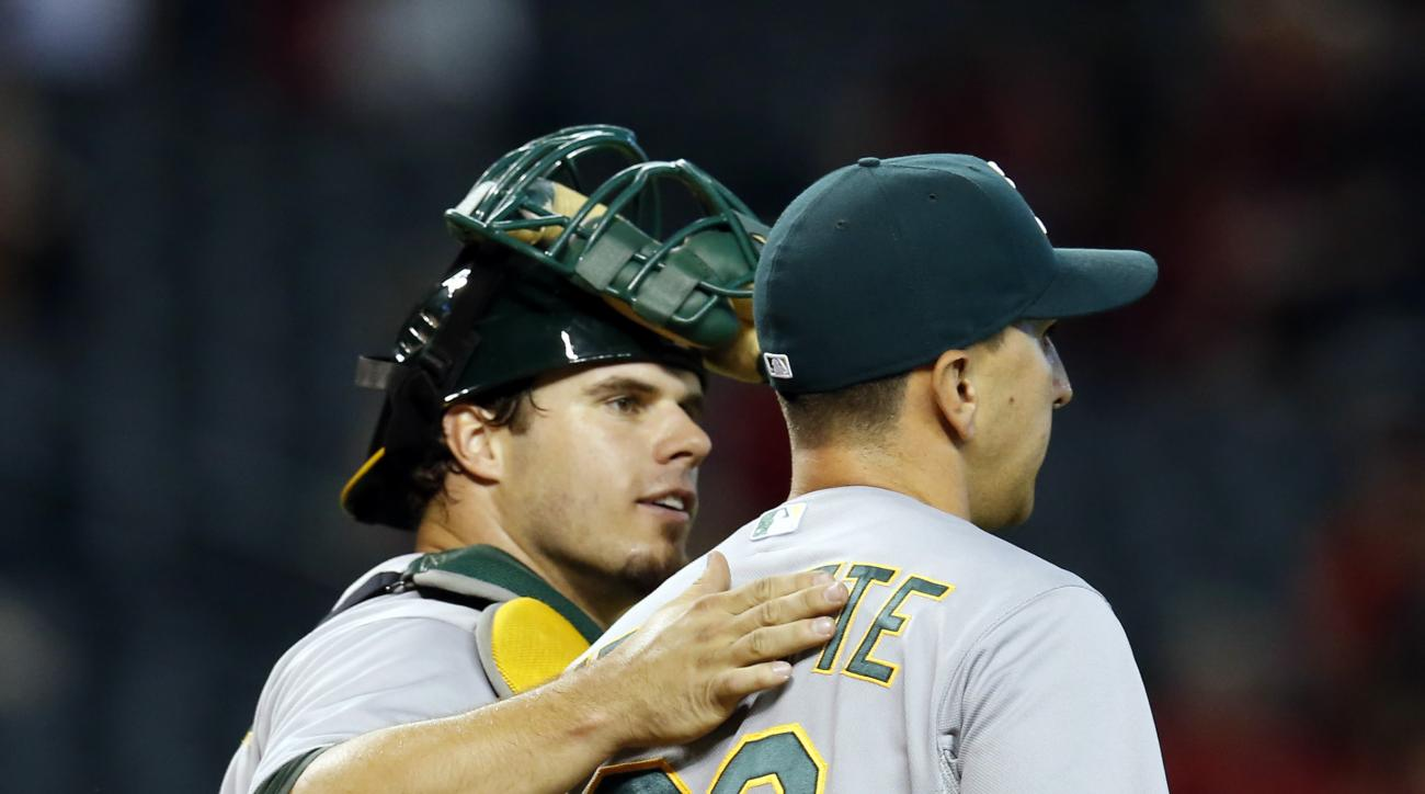 Oakland Athletics catcher Josh Phegley and Pat Venditte (29) celebrate after defeating the Arizona Diamondbacks 7-4 during a baseball game, Sunday, Aug. 30, 2015, in Phoenix. (AP Photo/Rick Scuteri)