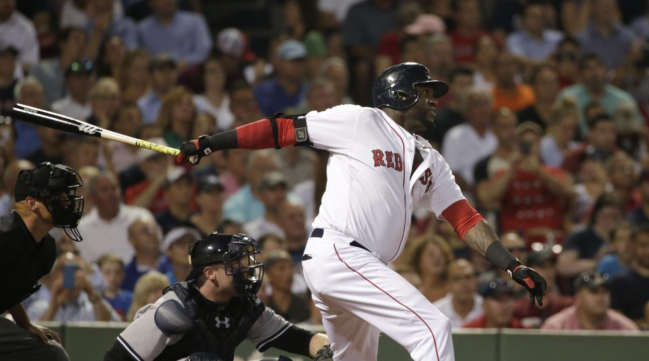 Boston Red Sox designated hitter David Ortiz, right, follows through on his swing as he hits a home run while New York Yankees catcher Brian McCann, left, looks on in the fourth inning of a baseball game, Monday, Aug. 31, 2015, at Fenway Park, in Boston.
