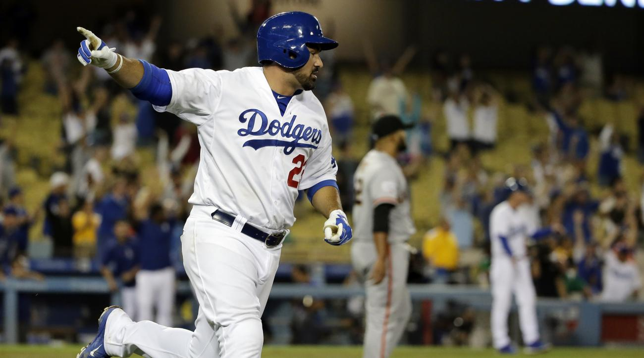 Los Angeles Dodgers' Adrian Gonzalez celebrates after scoring the game winning run on a single against the San Francisco Giants during the 14th inning of a baseball game in Los Angeles, Tuesday, Sept. 1, 2015. (AP Photo/Chris Carlson)