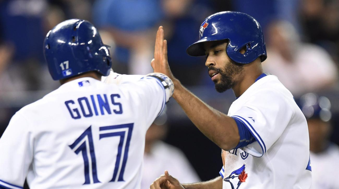 Toronto Blue Jays' Dalton Pompey celebrates with Ryan Goins after scoring against the Cleveland Indians during seventh inning of a baseball game Tuesday, Sept. 1, 2015, in Toronto. (Frank Gunn/The Canadian Press via AP)