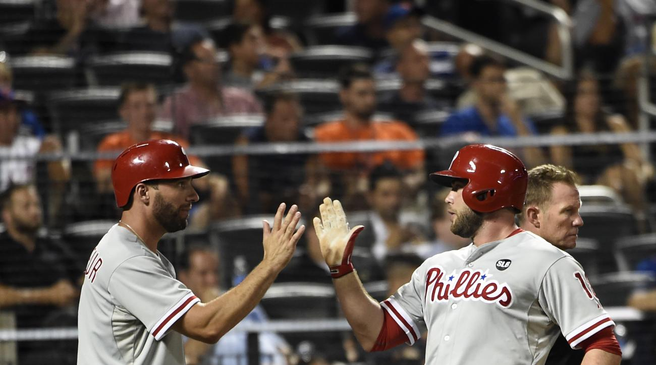 Philadelphia Phillies' Jeff Francoeur, left, high-fives Darin Ruf after they scored on Andres Blanco's double off of New York Mets relief pitcher Carlos Torres during the sixth inning of a baseball game Tuesday, Sept. 1, 2015, in New York. (AP Photo/Kathy