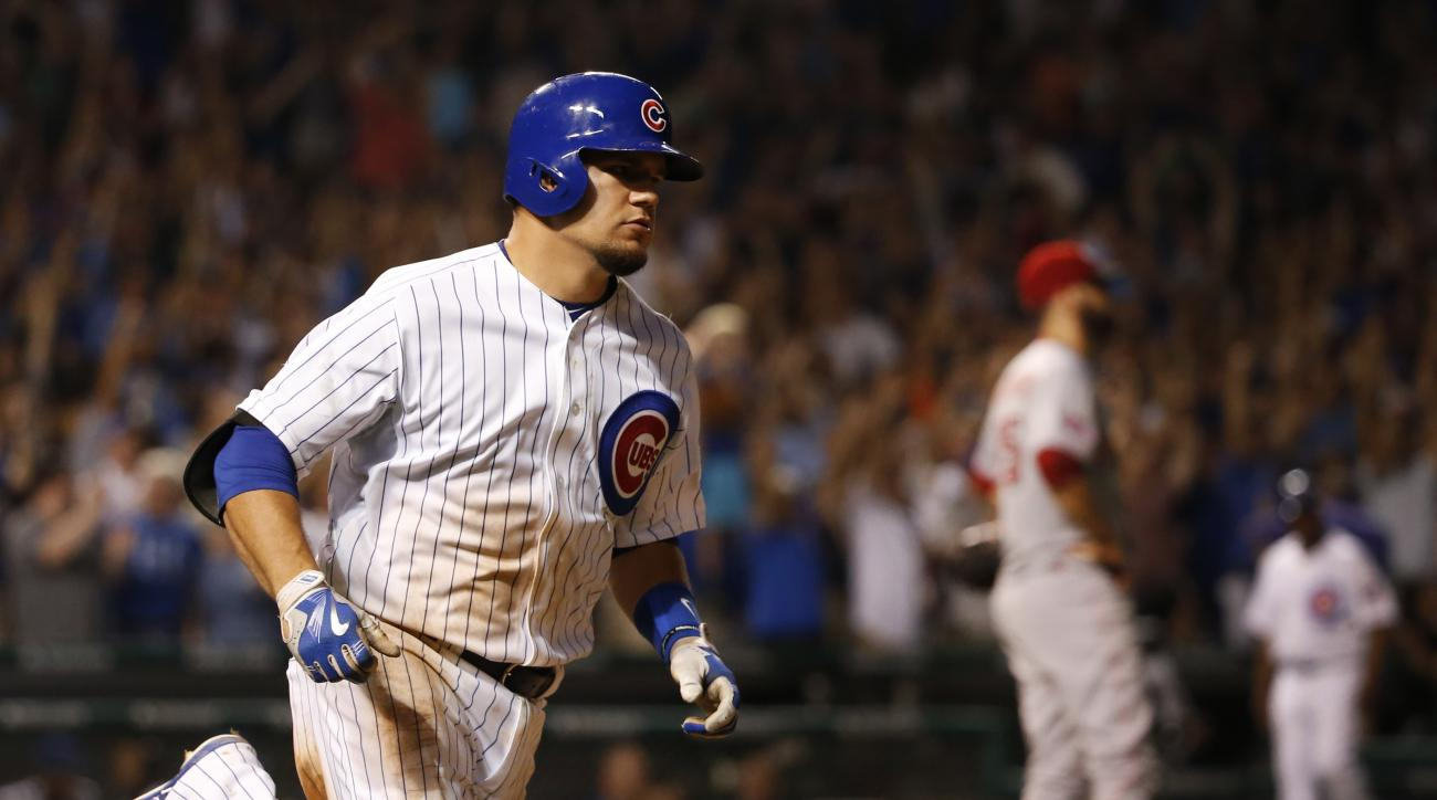 Chicago Cubs' Kyle Schwarber rounds the bases after hitting a two-run home run off Cincinnati Reds relief pitcher Burke Badenhop, right, also scoring Dexter Fowler, during the seventh inning of a baseball game Tuesday, Sept. 1, 2015, in Chicago. (AP Photo