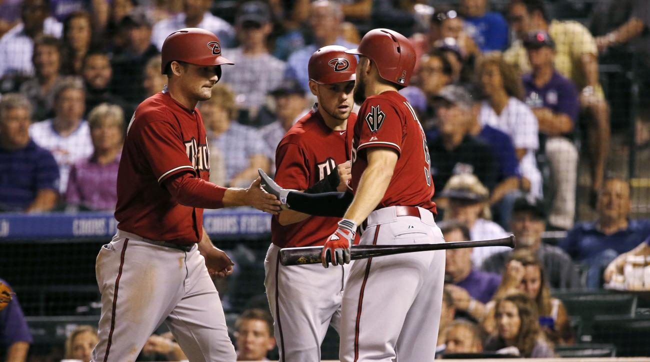 Arizona Diamondbacks' Ender Inciarte (5) greets Phil Gosselin and Chris Owings after scoring on a Aaron Hill two run double during the seventh inning of the second game of a baseball doubleheader Tuesday, Sept. 1, 2015, in Denver. (AP Photo/Jack Dempsey)
