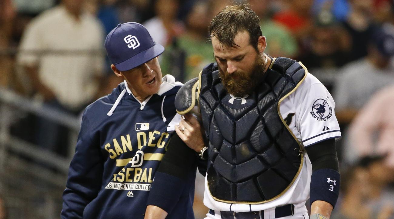 San Diego Padres catcher Derek Norris is helped from the field after being injured attempting to tag a Texas Rangers' runner at home plate in the seventh inning of a baseball game Tuesday, Sept. 1, 2015, in San Diego. (AP Photo/Lenny Ignelzi)