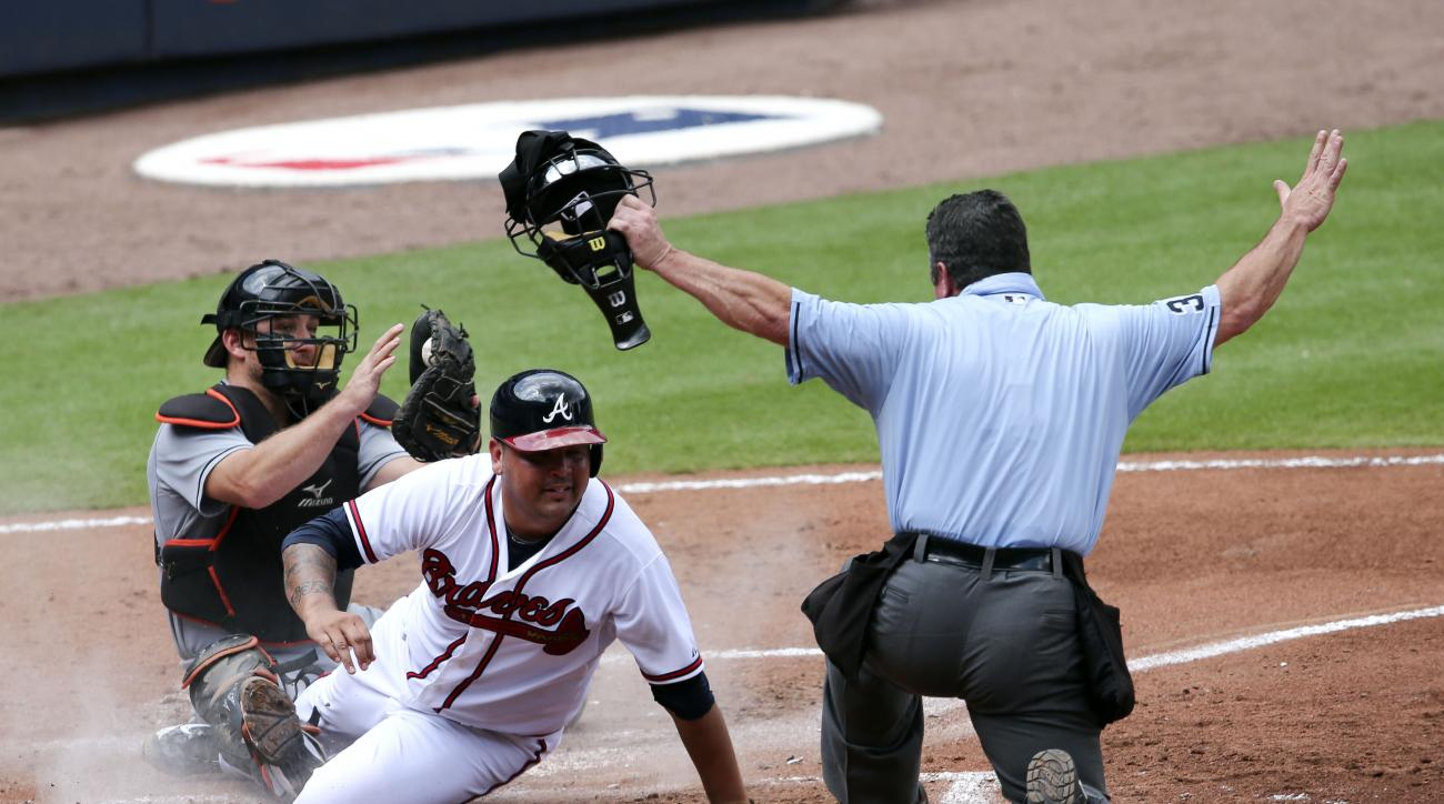 Atlanta Braves starting pitcher Williams Perez (61) scores past Miami Marlins catcher Jeff Mathis (6) on an Adonis Garcia sacrifice in the third a inning of a baseball game Wednesday, Sept. 2, 2015, in Atlanta. (AP Photo/John Bazemore)