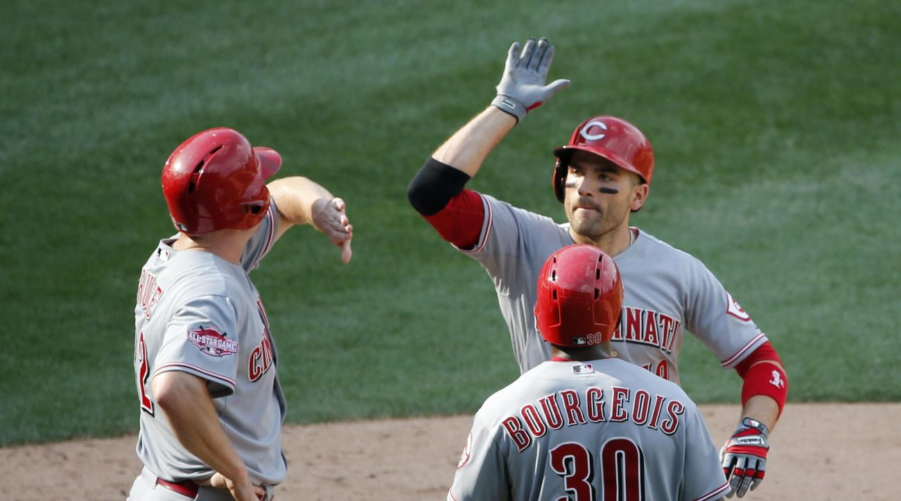 Cincinnati Reds' Joey Votto, top right, Jason Bourgeois (30) and Jay Bruce, celebrate after the trio scored on Votto's home run off Chicago Cubs relief pitcher Hector Rondon, during the ninth inning of a baseball game Wednesday, Sept. 2, 2015, in Chicago.