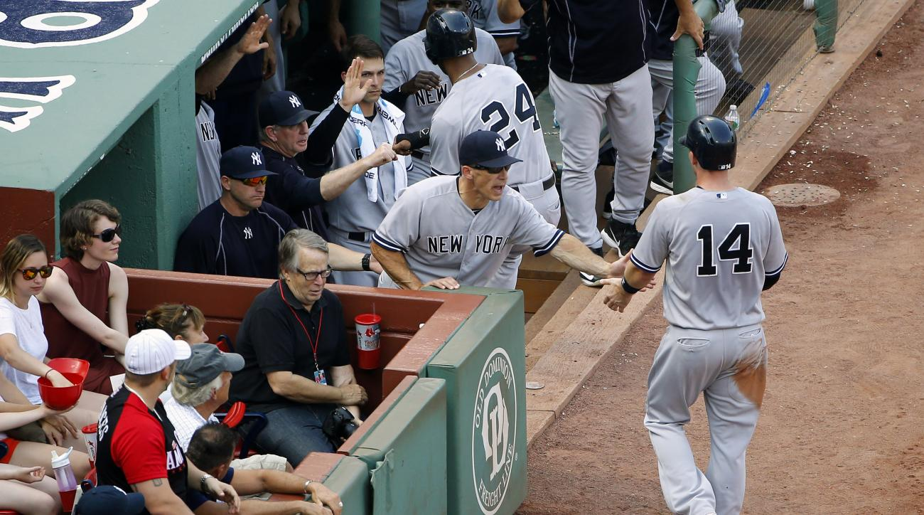 Fans watch as New York Yankees manager Joe Girardi congratulate Stephen Drew (14) and teammates congratulate Chris Young (24) after they both scored on a two-run single by Alex Rodriguez during the second inning of a baseball game against the Boston Red S