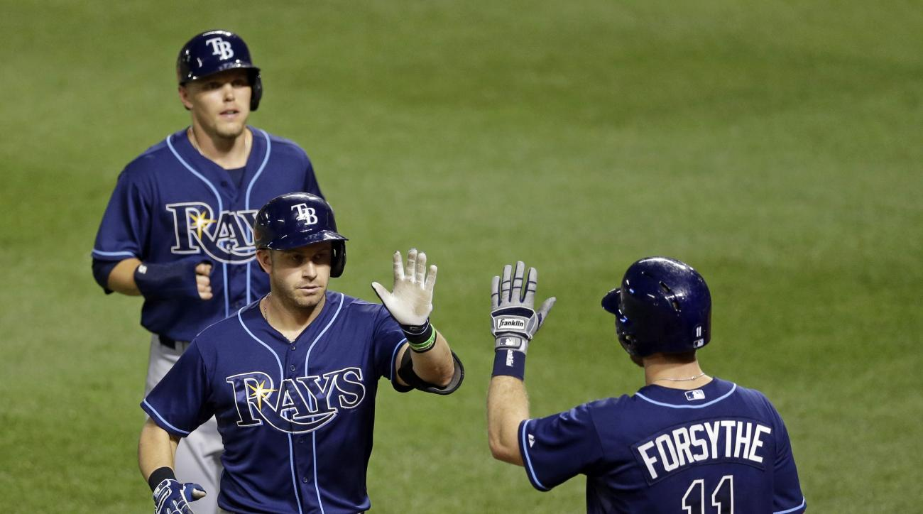Tampa Bay Rays' Evan Longoria, bottom left, and Brandon Guyer are greeted by teammate Logan Forsythe after Longoria batted Guyer in on a home run in the third inning of a baseball game against the Baltimore Orioles, Wednesday, Sept. 2, 2015, in Baltimore.