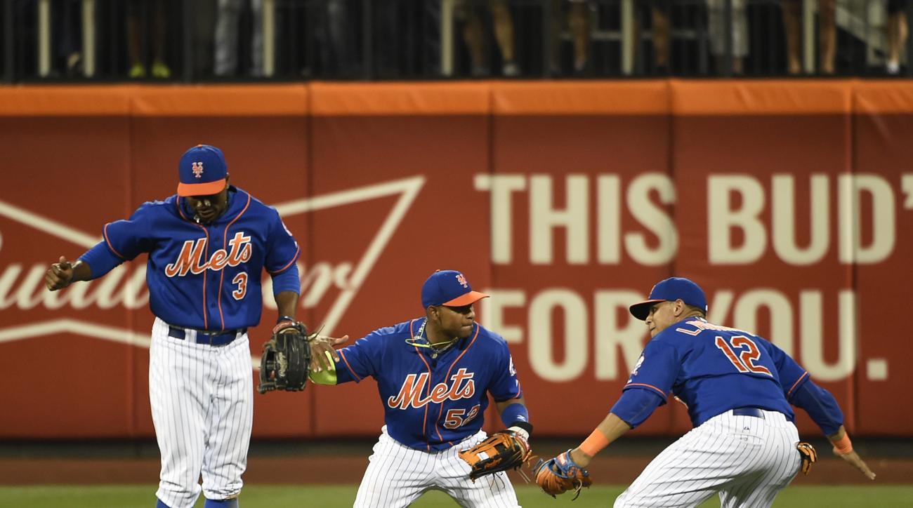 New York Mets' Curtis Granderson (3),  Yoenis Cespedes (52) and Juan Lagares celebrate the Mets' 9-4 win over the Philadelphia Phillies in a baseball game Wednesday, Sept. 2, 2015, in New York. (AP Photo/Kathy Kmonicek)