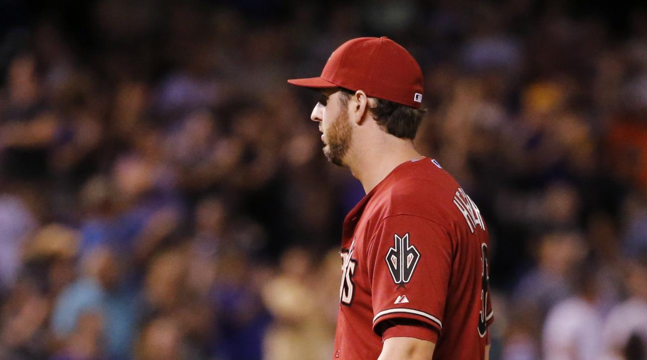 Arizona Diamondbacks relief pitcher Keith Hessler waits as Colorado Rockies' Carlos Gonzalez rounds the bases after hitting a grand slam during the seventh inning of a baseball game Wednesday, Sept. 2, 2015, in Denver. (AP Photo/Jack Dempsey)