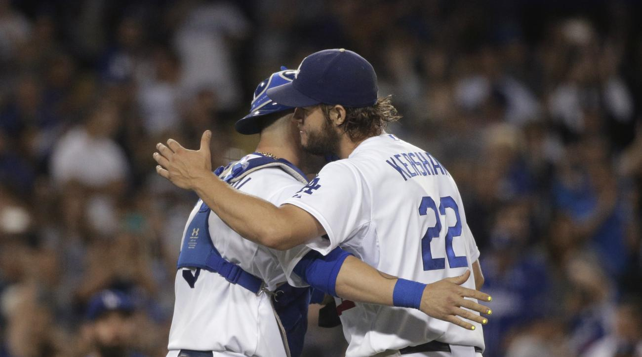 Los Angeles Dodgers starting pitcher Clayton Kershaw, right, and catcher Yasmani Grandal celebrate their team's 2-1 win against the San Francisco Giants in a baseball game, Wednesday, Sept. 2, 2015, in Los Angeles. (AP Photo/Jae C. Hong)