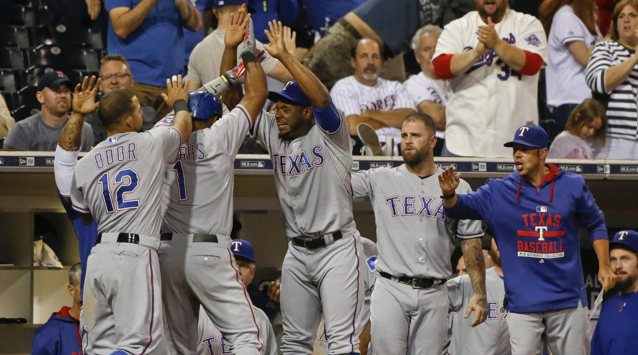 Texas Rangers players celebrate with Elvis Andrus, second from left,  after he scored the go ahead run against the San Diego Padres in the tenth inning of a baseball game Wednesday, Sept. 2, 2015, in San Diego. (AP Photo/Lenny Ignelzi)