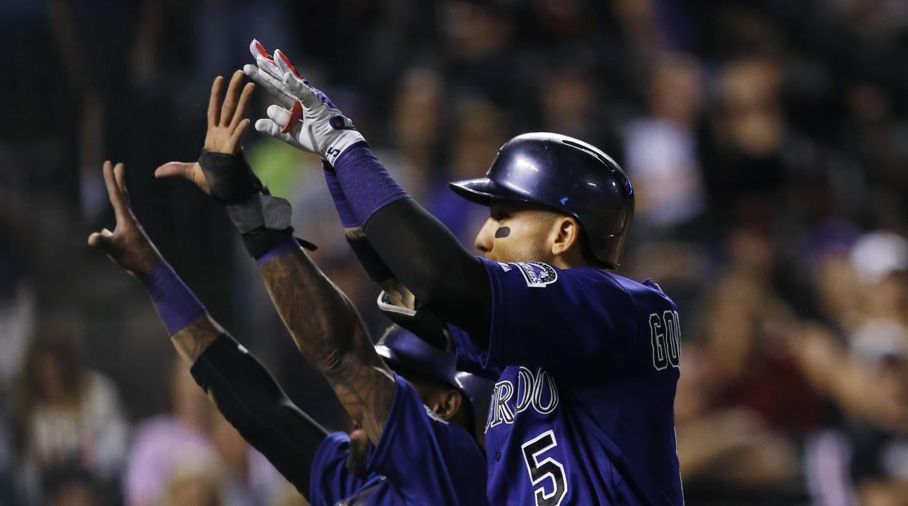 Colorado Rockies' Carlos Gonzalez, front, celebrates his two-run home run with teammate Jose Reyes against the San Francisco Giants in the fourth inning of a baseball game, Thursday, Sept.. 3, 2015, in Denver. (AP Photo/David Zalubowski)
