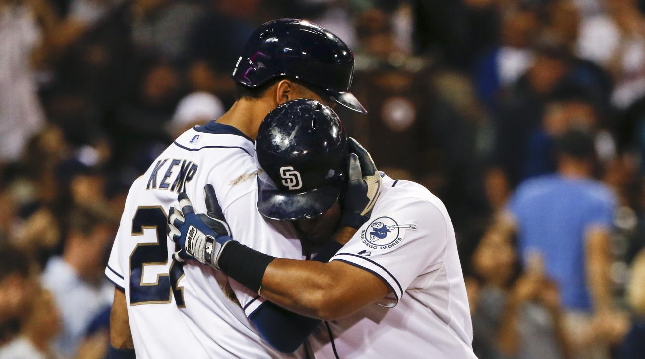 San Diego Padres' Yangervis Solarte gets a hug from Matt Kemp after his solo home run against the Los Angeles Dodgers during the seventh inning of a baseball game Thursday, Sept. 3, 2015, in San Diego. (AP Photo/Lenny Ignelzi)
