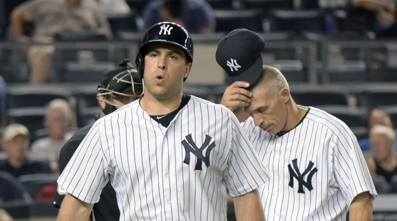 New York Yankees' Mark Teixeira reacts after fouling a ball off his leg as manager Joe Girardi, right, reacts during the sixth inning of a baseball game against the Minnesota Twins Monday, Aug 17, 2015, at Yankee Stadium in New York. Teixeira had to leave