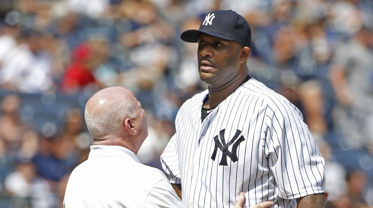 New York Yankees trainer Steve Donohue, left, talks to New York Yankees starting pitcher CC Sabathia on the mound in the third inning before New York Yankees manager Joe Girardi removed Sabathia from the baseball game against the Cleveland Indians at Yank