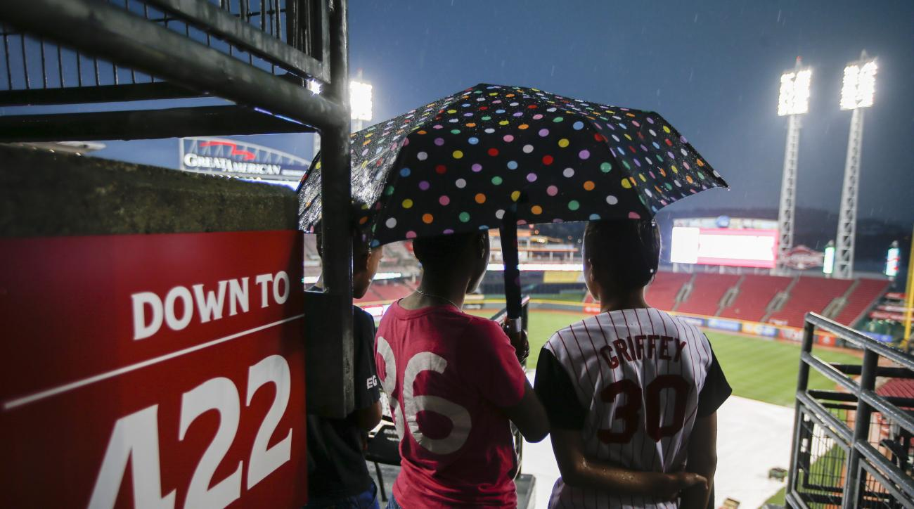 Fans stand under an umbrella during a rain delay before a baseball game between the Cincinnati Reds and the Milwaukee Brewers, Friday, Sept. 4, 2015, in Cincinnati. (AP Photo/John Minchillo)