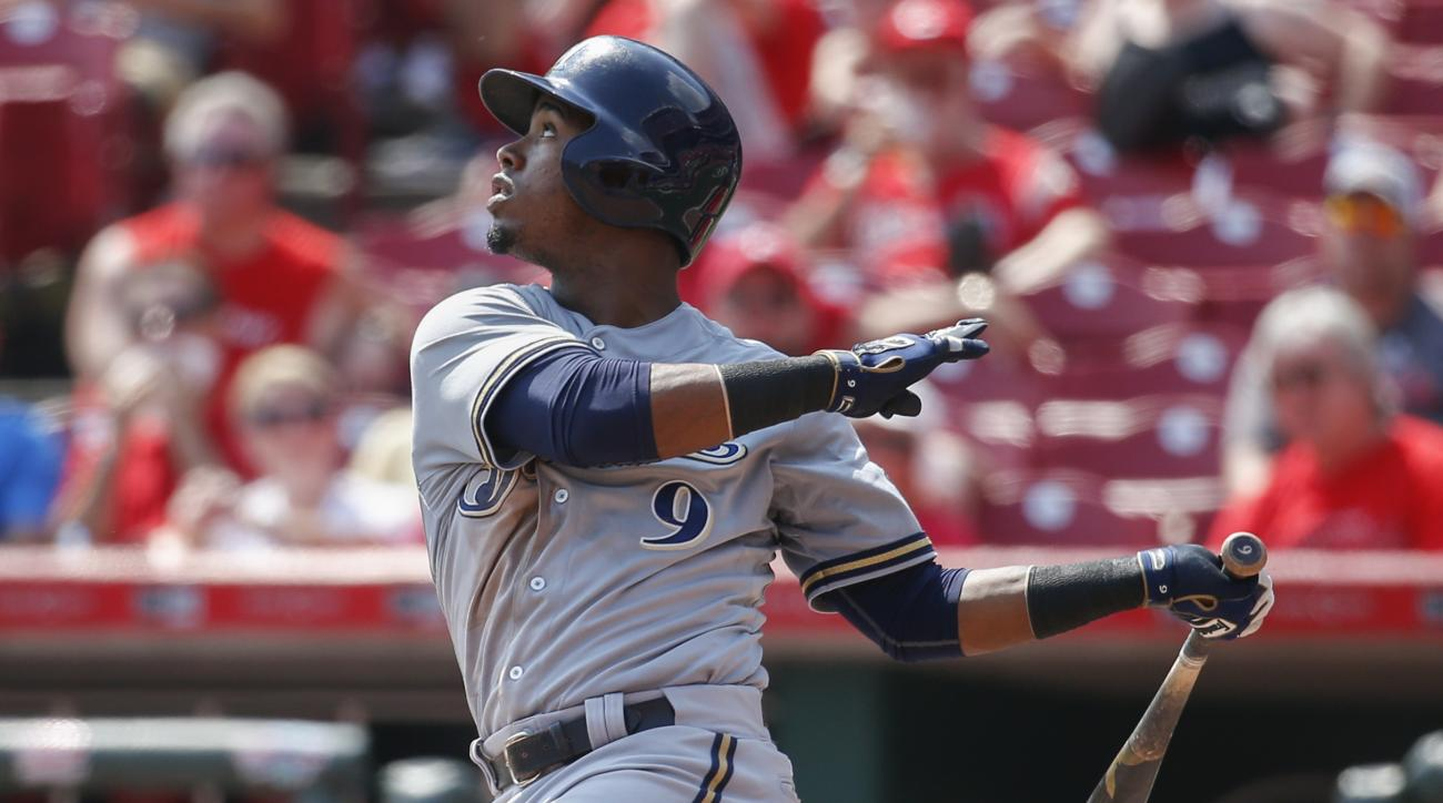 Milwaukee Brewers' Jean Segura hits an RBI single off Cincinnati Reds starting pitcher John Lamb to drive in Elian Herrera in the fifth inning in the first game of a baseball doubleheader, Saturday, Sept. 5, 2015, in Cincinnati. (AP Photo/John Minchillo)
