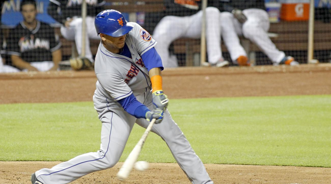 New York Mets' Juan Lagares hits a sixth inning single before being tagged out trying to reach second during play against the Miami Marlins in their baseball game in Miami, Saturday, Sept. 5, 2015. (AP Photo/Joe Skipper)
