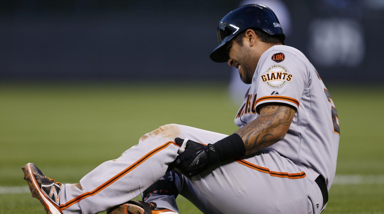 San Francisco Giants' Hector Sanchez falls and grabs his knee after running out a sacrifice bunt against the Colorado Rockies in the fourth inning of a baseball game Saturday, Sept. 5, 2015, in Denver. Sanchez was helped from the field and left the game.