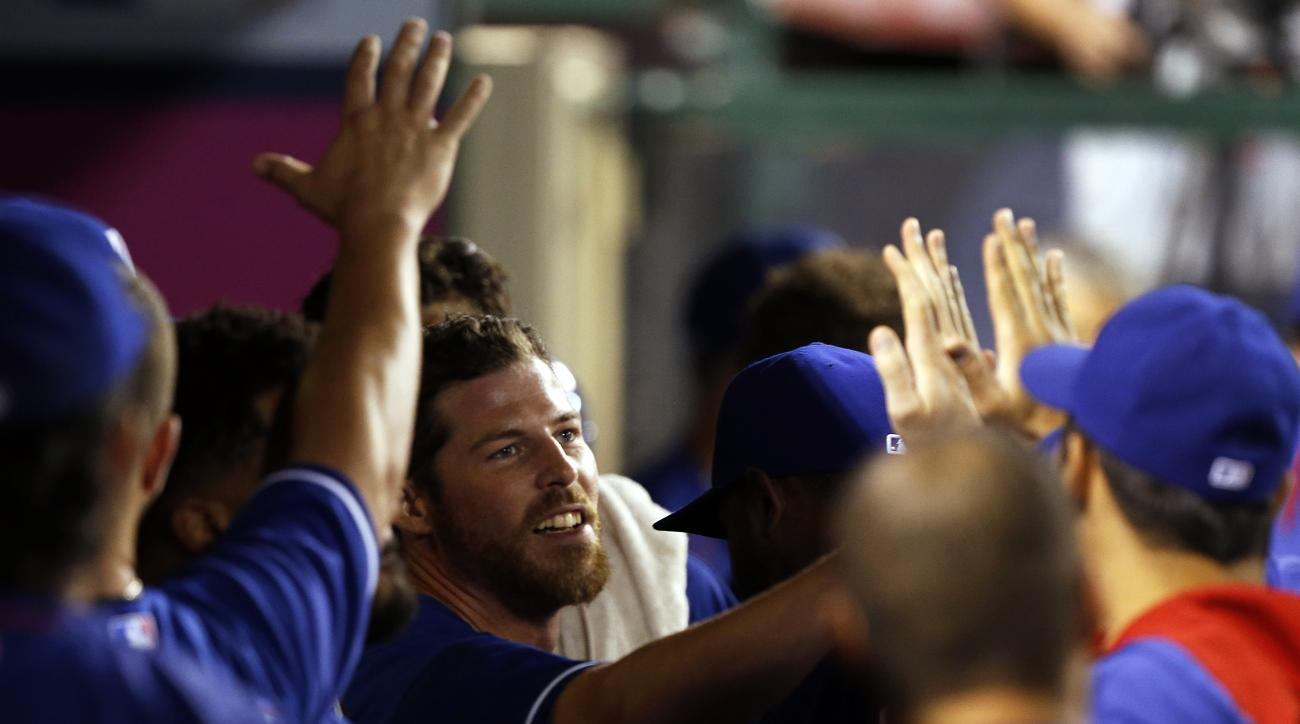 Texas Rangers' Ryan Strausborger, center, gets high-fives from teammates after scoring on a sacrifice fly hit by Delino DeShields during the eighth inning of a baseball game against the Los Angeles Angels in Anaheim, Calif., Saturday, Sept. 5, 2015. (AP P