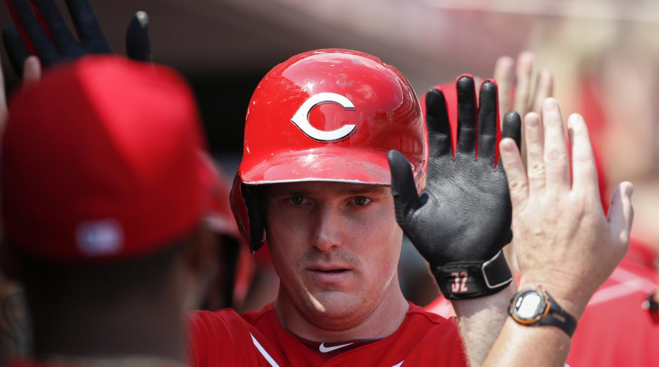 Cincinnati Reds' Jay Bruce celebrates in the dugout after hitting a two-run home run off Milwaukee Brewers starting pitcher Jimmy Nelson in the fifth inning of a baseball game, Sunday, Sept. 6, 2015, in Cincinnati. (AP Photo/John Minchillo)