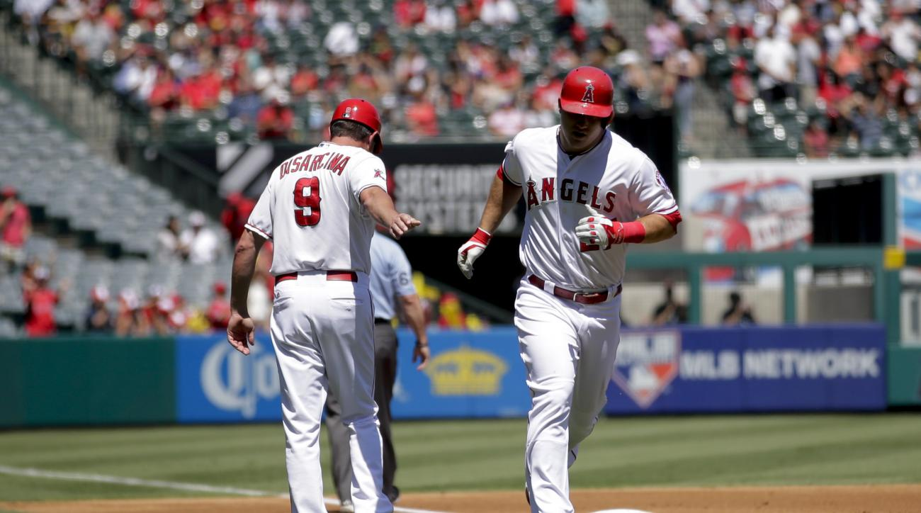 Los Angeles Angels' Mike Trout, right, is congratulated by third base coach Gary DiSarcina after hitting a home run against the Texas Rangers during the first inning of a baseball game, Sunday, Sept. 6, 2015, in Anaheim, Calif. (AP Photo/Jae C. Hong)