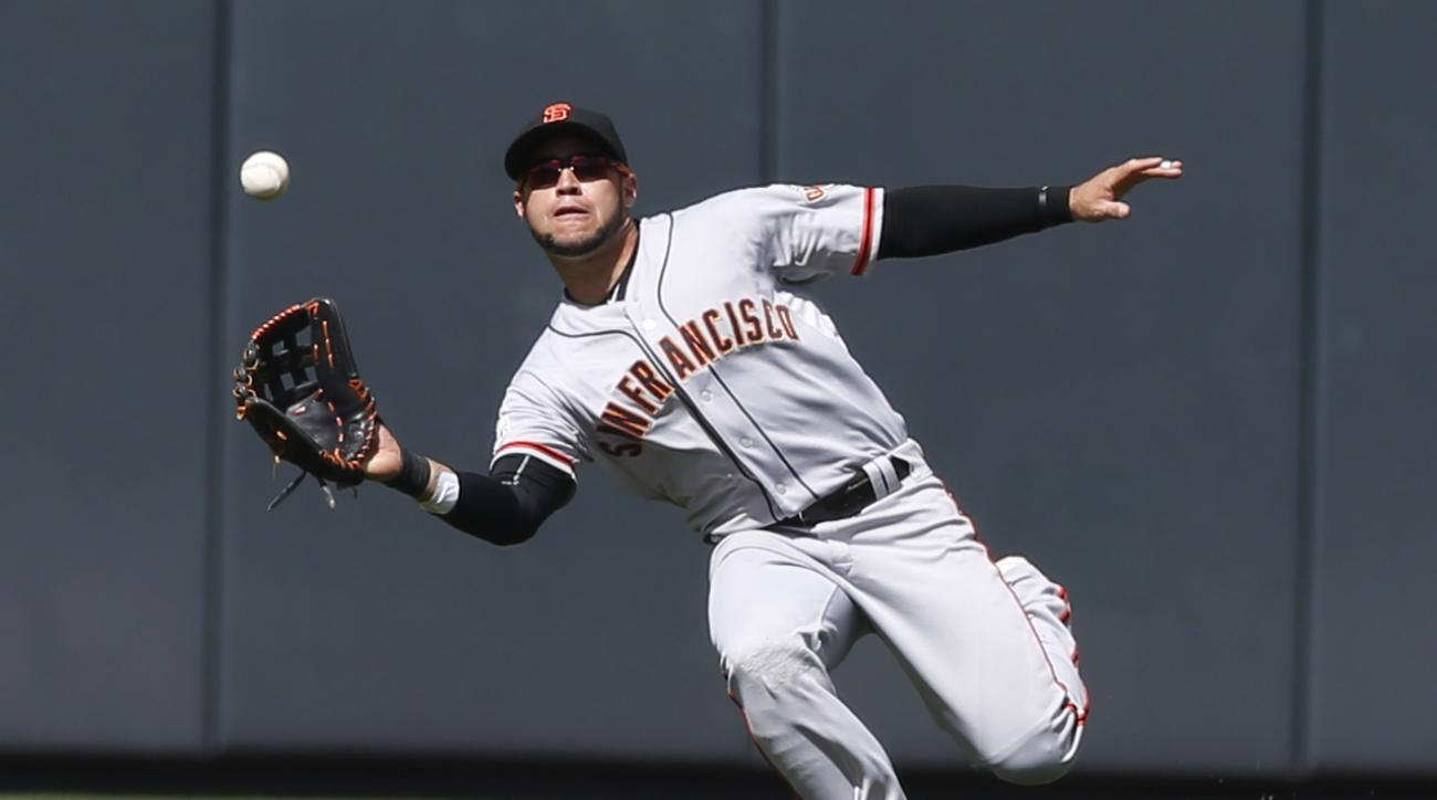 San Francisco Giants center fielder Gregor Blanco pulls in a sinking line drive off the bat of Colorado Rockies' Nick Hundley to end the first inning of a baseball game Sunday, Sept. 6, 2015, in Denver. (AP Photo/David Zalubowski)