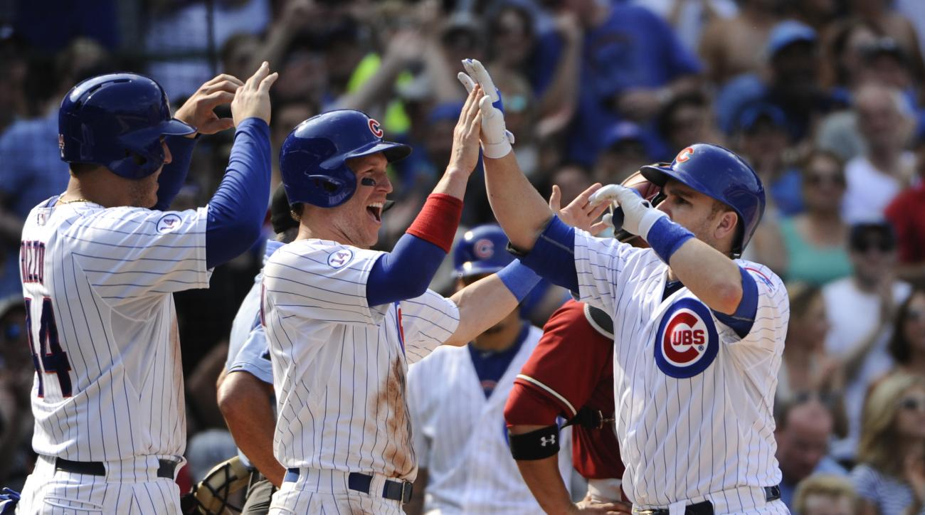 Chicago Cubs' Anthony Rizzo (44), left, and Chris Coghlan, center, high-five teammate Miguel Montero after he hit a grand slam off Arizona Diamondbacks' Matt Reynolds pitching in the sixth inning of a baseball game on Sunday, Sept. 6, 2015, in Chicago. (A