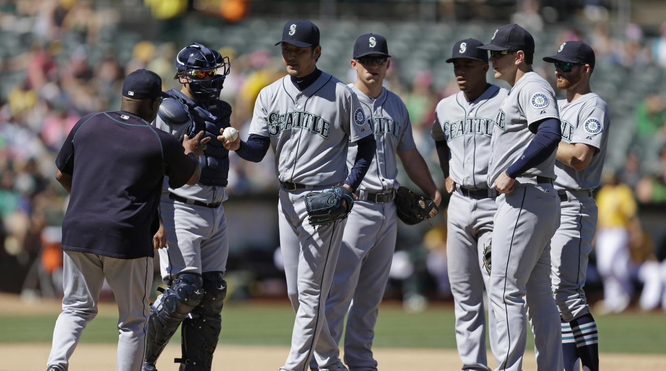 Seattle Mariners pitcher Hisashi Iwakuma, third from left, hands the ball to manager Lloyd McClendon, left, as he is removed in the seventh inning of a baseball game against the Oakland Athletics, Sunday, Sept. 6, 2015, in Oakland, Calif. (AP Photo/Ben Ma