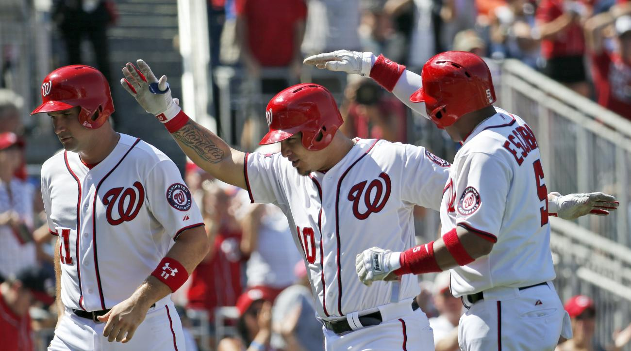 Washington Nationals' Ryan Zimmerman, left, Wilson Ramos, and Yunel Escobar, celebrate scoring on Ramos' grand slam during the fourth inning of a baseball game against the New York Mets  at Nationals Park, Monday, Sept. 7, 2015, in Washington. (AP Photo/A