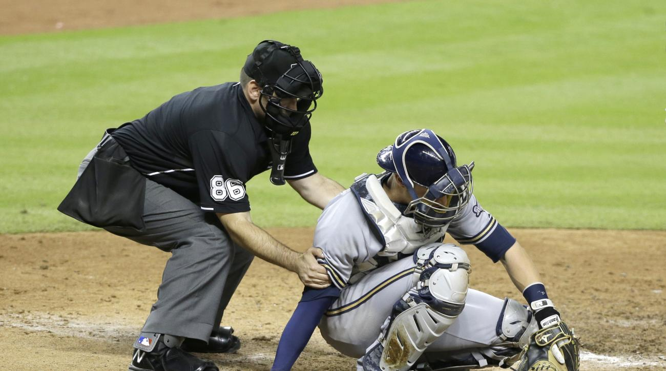 Home plate umpire David Rackley (86) helps Milwaukee Brewers catcher Jonathan Lucroy up after a foul tip hit Lucroy during the seventh inning of a baseball game against the Miami Marlins, Tuesday, Sept. 8, 2015, in Miami. The Marlins defeated the Brewers