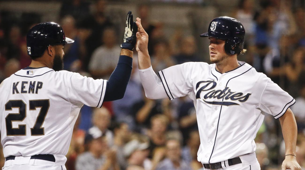 San Diego Padres' Wil Myers, right, high-fives Matt Kemp after opening the scoring with a solo home run against the Colorado Rockies during the sixth inning of a baseball game Tuesday, Sept. 8, 2015, in San Diego. (AP Photo/Lenny Ignelzi)
