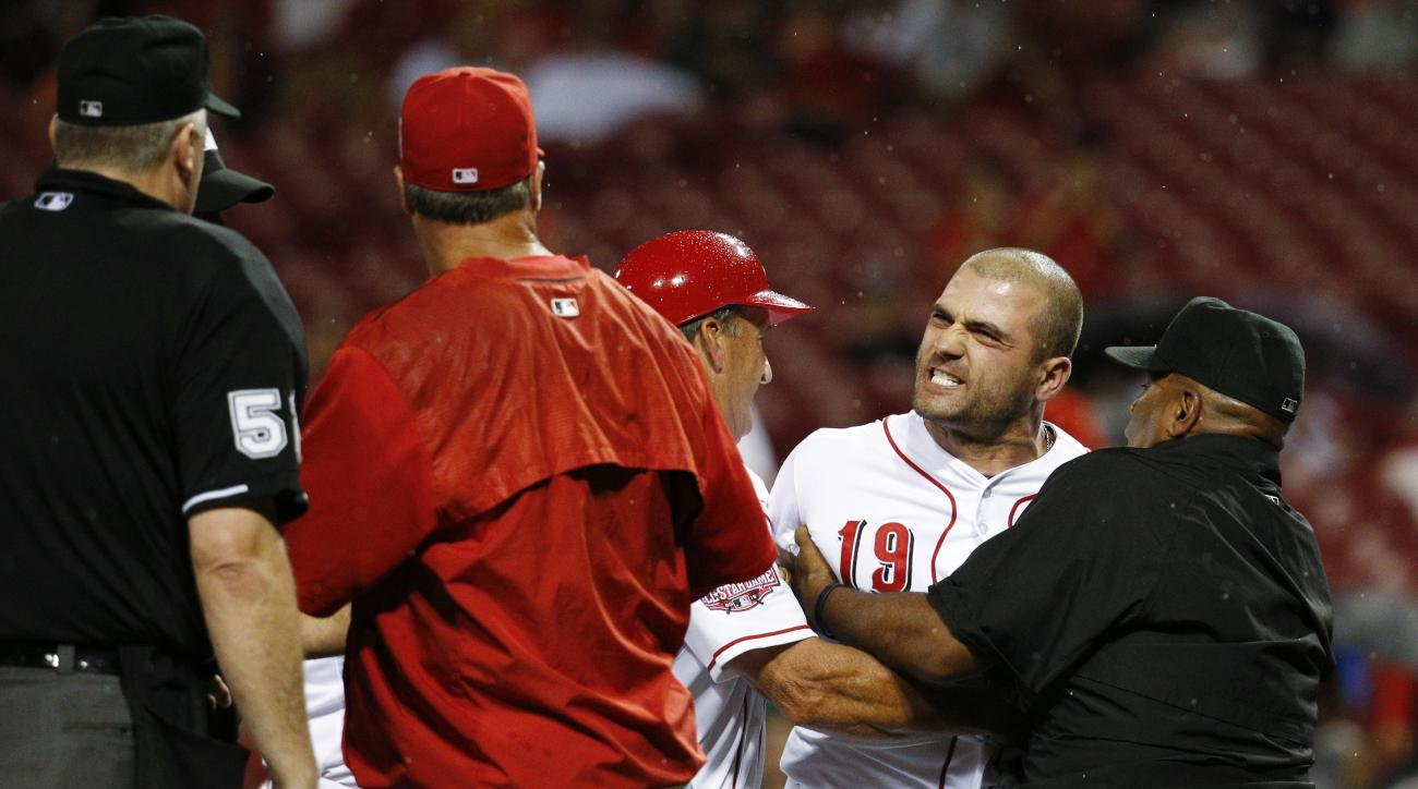 Cincinnati Reds' Joey Votto (19) is restrained from umpire Bill Welke (52) after being thrown out of the baseball game for arguing balls and strikes during the eighth inning Wednesday, Sept. 9, 2015, in Cincinnati. (AP Photo/John Minchillo)