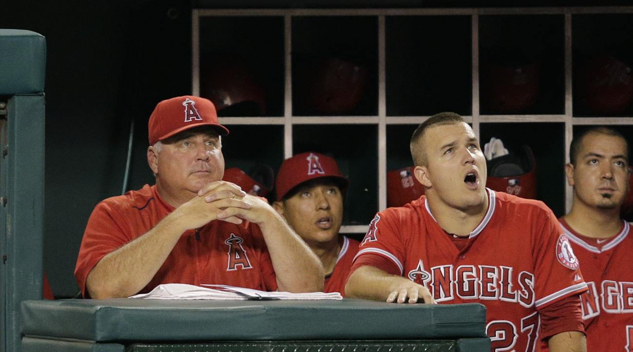 Los Angeles Angels manager Mike Scioscia, left, and player Mike Trout, right, watch a foul ball hit by Carlos Perez during the second inning of a baseball game against the Los Angeles Dodgers, Wednesday, Sept. 9, 2015, in Anaheim, Calif. (AP Photo/Jae C.