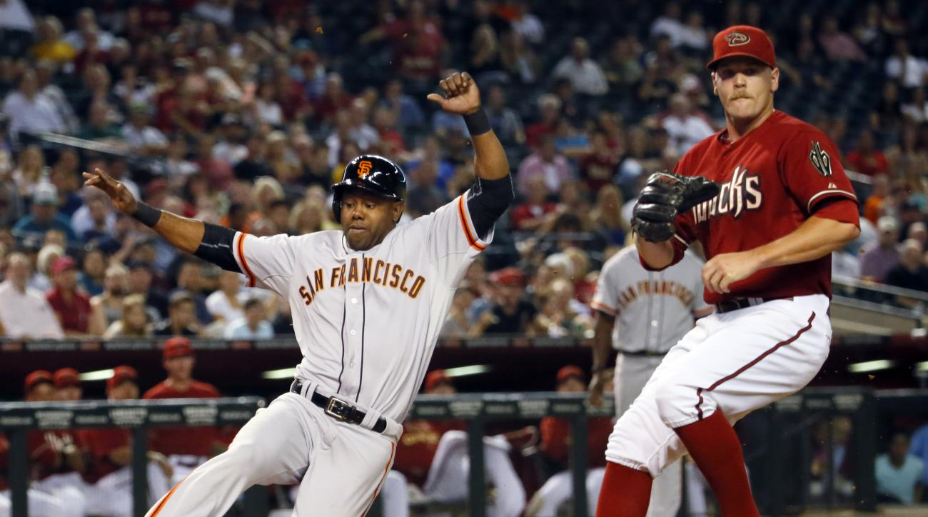 San Francisco Giants' Alejandro De Aza scores on a wild pitch as Arizona Diamondbacks pitcher Andrew Chafin waits for the throw during the sixth inning of a baseball game, Wednesday, Sept. 9, 2015, in Phoenix. (AP Photo/Matt York)