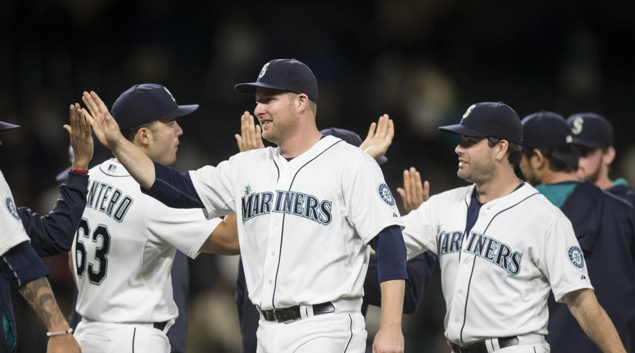 Seattle Mariners' Mark Trumbo, center, and teammates, including Jesus Montero, left, and Seth Smith, celebrate following a baseball game against the Texas Rangers, Wednesday, Sept. 9, 2015, in Seattle. The Mariners won 6-0 . (AP Photo/Stephen Brashear)