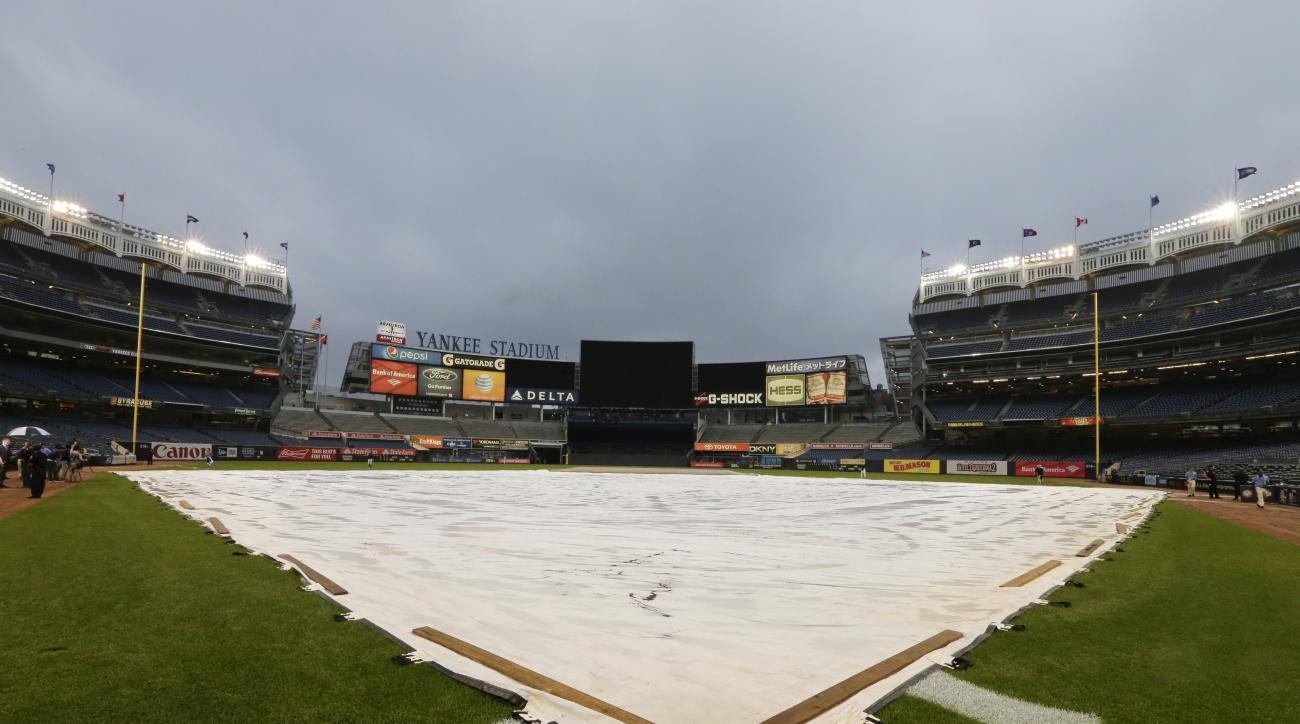A tarp covers the field at Yankee Stadium as a baseball game between the New York Yankees and the Toronto Blue Jays has been postponed due to inclement weather Thursday, Sept. 10, 2015, in New York. (AP Photo/Frank Franklin II)
