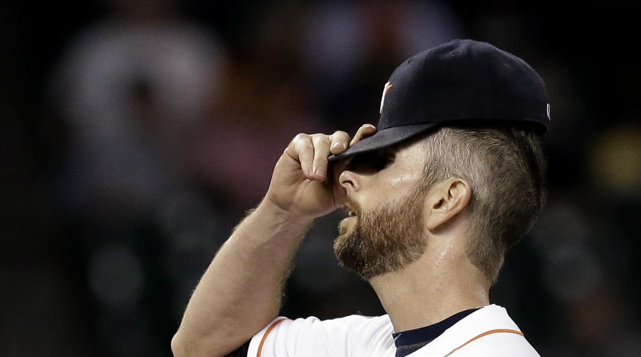 Houston Astros starting pitcher Scott Feldman adjusts his cap after giving up a walk to Seattle Mariners' Ketel Marte to load the bases during the second inning of a baseball game Tuesday, Sept. 1, 2015, in Houston. (AP Photo/Pat Sullivan)