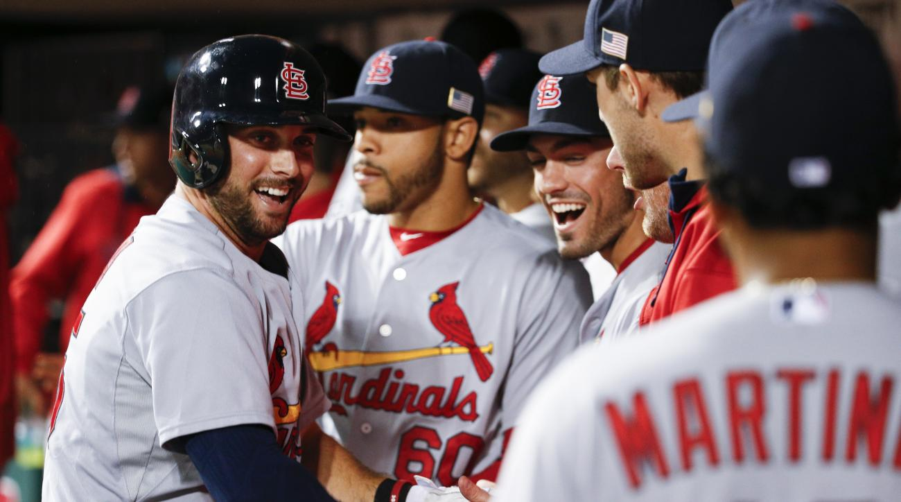St. Louis Cardinals' Greg Garcia, left, celebrates in the dugout after hitting a solo home run off Cincinnati Reds starting pitcher Michael Lorenzen during the fourth inning of a baseball game, Friday, Sept. 11, 2015, in Cincinnati. (AP Photo/John Minchil