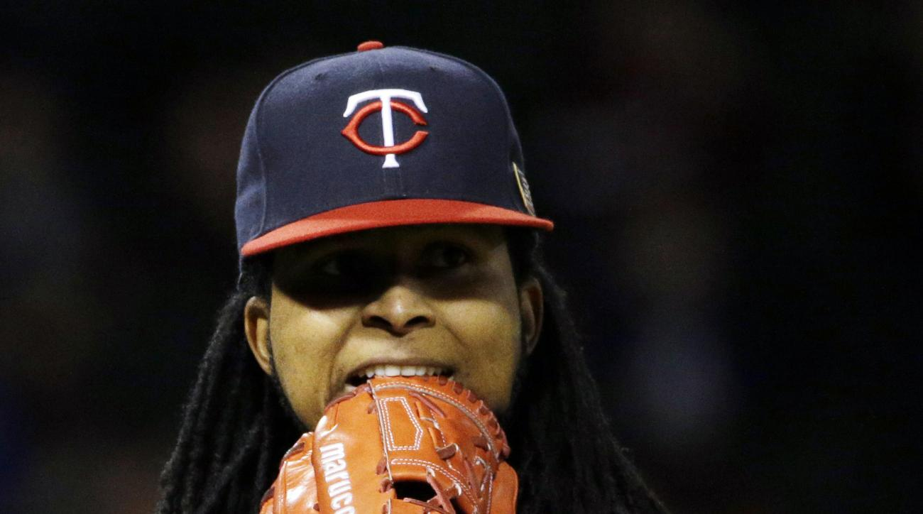 Minnesota Twins starter Ervin Santana bites his glove as he walks back to the dugout after the fifth inning of a baseball game against the Chicago White Sox, Friday, Sept. 11, 2015, in Chicago. (AP Photo/Nam Y. Huh)
