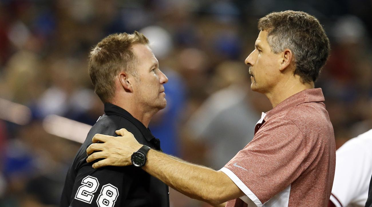Umpire Jim Wolf (28) gets examined by Arizona Diamondbacks trainer Ken Crenshaw after getting hit with a foul ball during the second inning of the Diamondbacks' baseball game against the Los Angeles Dodgers, Friday, Sept. 11, 2015, in Phoenix. (AP Photo/R